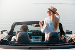Finally arrived!. Rear view of smiling young women enjoying scenery while her boyfriend sitting near on front seat of their convertible Stock Photography