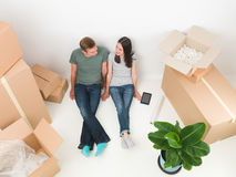 Finally we can afford our own house. Happy young couple lying on floor with boxes around them. moving house Stock Images