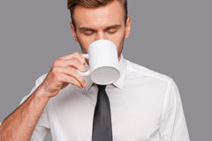 Finally coffee break. Tired young man in formalwear holding coffee cup and drinking it while standing against grey background Stock Photo