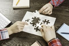 Finally finding solution. Group of people sitting at table and assembling jigsaw puzzle Royalty Free Stock Photo