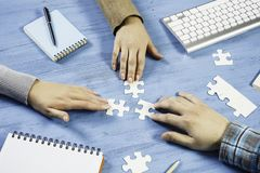 Finally finding solution. Group of people sitting at table and assembling jigsaw puzzle Stock Photo