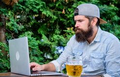 Finally friday. Hipster relax sit terrace with beer. Bearded hipster freelancer enjoy end of working day with beer mug stock photography