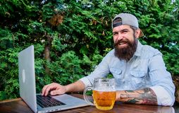 Finally friday. Hipster relax sit terrace outdoors with beer. Bearded hipster freelancer enjoy end of working day with. Beer mug. He deserve this pint. Brutal stock image