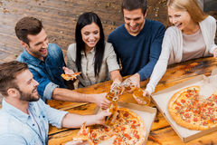 Finally it is Friday!. Top view of five joyful young people clinking glasses with beer and eating pizza while standing outdoors Stock Photo