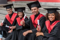 Glad young students sitting on steps in graduation clothes. Finally we got a diploma. Portrait of happy graduates showing certificate of high education and Royalty Free Stock Image