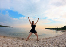 Finally holiday. A woman in a strong position in a black dress on the beach. Istria, Croatia Royalty Free Stock Photo