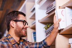 Finally I found this book. Happy young man choosing book from bookshelf and smiling while standing in library Stock Image