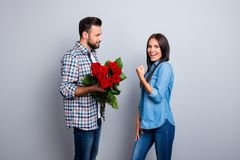 Finally, at last he did it! Man with bristle prepare bouquet of. Red roses to his excited, happy girlfriend who raised fist, looking at camera, celebrating a Stock Photography