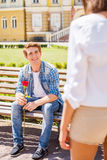 Finally meet!. Happy young men sitting on the bench and holding single rose with women on foreground Royalty Free Stock Image