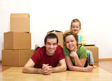 Finally in our new home. Young family laying on the floor among cardboard boxes, moving concept Stock Photos