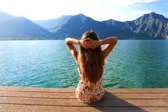 Finally relax! Beautiful lifestyle woman sitting and relaxing on the shore of lake contemplating amazing landscape. Contemplating. Back view of attractive girl stock photos