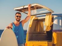 Finally summer!. Smiling young man leaning at the skimboard and holding hand on door of car trunk while standing on the beach Stock Image