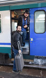 Finally the train is here. Two male tourists are getting on the train with bags and suitcase. Background of the train-station, waiting for their bus/train Royalty Free Stock Photography
