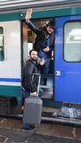 Finally the train is here. Waving goodbye. Two male tourists are getting on the train with bags and suitcase. Background of the train-station, waiting for their Royalty Free Stock Photography