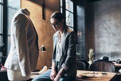 Finally work is done. Tired young woman in eyewear leaning on th. E desk while spending time in her workshop Royalty Free Stock Image