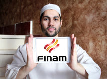 Finam Holdings logo. Logo of Finam Holdings on samsung tablet holded by arab muslim man. Finam Holdings is a financial services company headquartered in Moscow Stock Photos