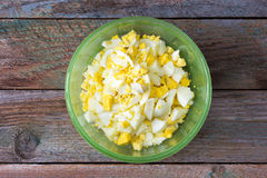 Finamente - ovos cozidos desbastados na placa verde na tabela de madeira velha Foto de Stock Royalty Free