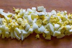 Finamente - ovos cozidos desbastados no meio de uma placa de corte de madeira velha Fotos de Stock