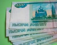 finança, economia, operação bancária, conceito - fim acima do pacote de cédulas do russo do dinheiro mil rublos no fundo verde fotografia de stock