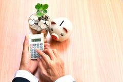 Finança, mão da pessoa que usa a calculadora com as moedas no vidro e Imagens de Stock