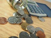 Finança, negócio, pilha das moedas, dinheiro tailandês nos produtos vidreiros, calculadora no fundo de madeira Fotos de Stock