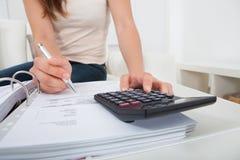 Finanças calculadoras da casa da mulher na tabela fotos de stock royalty free