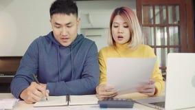 Finanças de controlo dos pares asiáticos novos, revendo suas contas bancárias usando o laptop e a calculadora na casa moderna video estoque