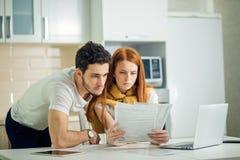 Finanças de controlo dos pares, revendo contas bancárias usando o laptop fotos de stock
