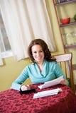 Finanças: A mulher senta-se em contas pagando da tabela Fotos de Stock Royalty Free