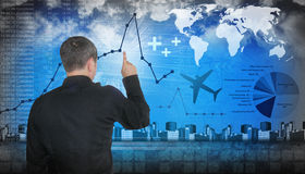 Finanace Travel Business Man Pointing. A business man is pointing at financial figures. There are line graphs and pie charts with data. There are also travel Stock Images