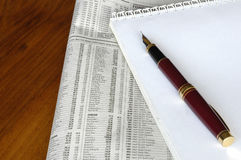 Finance 01. Fountain pen, financial newspaper and white notepad on a desktop Royalty Free Stock Images