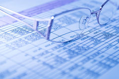 Finance. Glasses over financial graphs in blue light Royalty Free Stock Photography