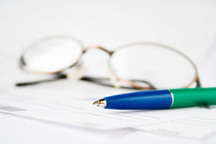 Finance. Pen and eyeglasses on top of financial statements Stock Photography