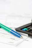 Finance. Pen and calculator on top of financial statements Royalty Free Stock Image