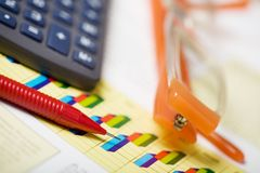 Finance. Close up of a calculator, financial figures, pen and eye glasses. Selective focus Stock Photos