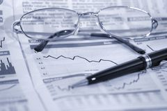 Finance. Financial graph, glasses and pen - selective focus Royalty Free Stock Photos