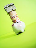 Finance. A house on top of money and piggy, metaphors for banking, finance stock photography