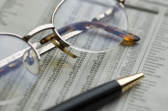 Finance. Pen and glasses on financial figures Stock Image