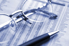Finance. Pen and glasses on financial figures. Duotone