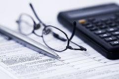 Finance. Close up of taxes form, glasses, calculator and pen Stock Images