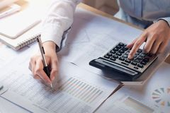 finance and accounting concept. business woman working on desk using calculator to calculate