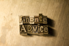 Finance advice - Metal typography lettering sign. Lead metal  typography text on wooden background Royalty Free Stock Photography