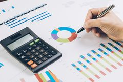 Finance, business budget planning or analysis concept, hand hold. Ing pen reviewing pie chart and graph information report with calculator on office desk royalty free stock photo