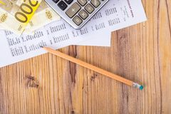 Euro Banknotes with Pencil and Calculator on Earning Report. Finance and business concept, two hundred euro banknotes with pencil and calculator on earning Stock Image