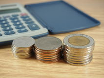 Finance business, pile of coins, money and calculator on wood background Royalty Free Stock Photos