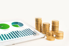 Finance and business report concept with coins and statistic on tablet Stock Image