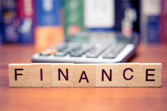 Finance. Calculator with the word Finance written in wooden block letters royalty free stock image