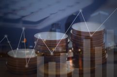 Finance, capital banking and investment concept, Double exporsur. E stacked of coins and night city with graph Royalty Free Stock Image