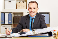 Finance clerk at desk with files Stock Photos