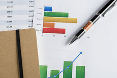 Finance color graphics with a pen and shedule papers. Royalty Free Stock Photos